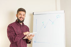 Bearded man presenting by the flipchart. Young bearded man presenting by the flipchart Stock Photography