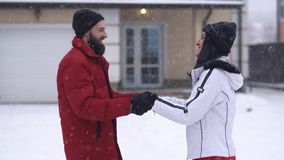 Bearded man and pretty woman kissing in winter backyard. Man trying to touch lips of girl with finger in glove, both. People laughing. Happy couple have a fun stock video
