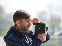 Bearded man professional cameraman observes and shoots an 8mm mo. Vie camera on a city street in the daytime Stock Photos