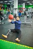 Bearded man with prosthetic leg catching ball. Content handsome young bearded man with prosthetic leg sitting on floor in modern gym with fitness equipment and stock photo