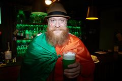 Bearded man in pub. Happy bearded man wrapped into irish flag cheering up with glass of beer in pub Royalty Free Stock Photography