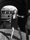 Bearded man pulls pretty girl. Bearded men hipster pulls pretty brunette girl young sexy women with slim body in black dress in town Stock Image