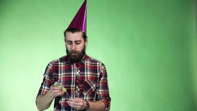 Bearded man putting on a party hat. Bearded man in a plaid shirt putting on a party hat to celebrate , upper body over a green background with copy space and stock footage