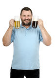 Bearded bartender raising two mugs of beer. White bearded bartender in blue polo shirt raising two mugs of beer Royalty Free Stock Images