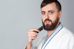 Bearded man with a razor Stock Images