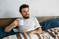 Bearded man reading a big book lying in his bedroom. Cute guy looking at the camera lifting cup of hot tea or coffee. He has really nice smile. Close up Royalty Free Stock Photos