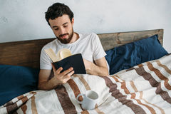 Bearded man reading a big book lying in his bedroom. Delighted guy reading some interesting story or romance. He is flipping pages really fast Royalty Free Stock Images