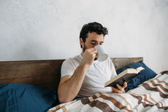 Bearded man reading a big book lying in his bedroom. Handsome man reading an exciting book while holding a cup of hot tea or coffee being in his bedroom. It is Royalty Free Stock Photos