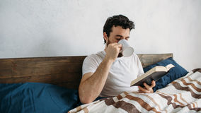 Bearded man reading a big book lying in his bedroom. Royalty Free Stock Photo