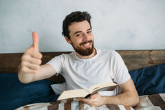 Bearded man reading a big book lying in his bedroom. Happy handsome guy showing thumb up and smiling at the camera. Close up Stock Images
