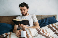 Bearded man reading a big book lying in his bedroom. Bearded man reading a big book lying in his bedroom and having some tasty drink in his cup. Handsome guy Stock Image