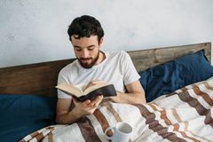 Bearded man reading a big book lying in his bedroom. Bearded man reading a big book lying in his bedroom putting cup on the blanket. Excited guy is absorbing Stock Photography