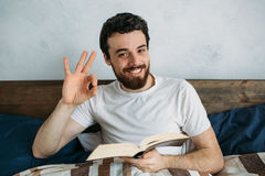 Bearded man reading a big book lying in his bedroom. Satisfied guy showing ok sign with one hand and looking at camera. Close up Stock Photo