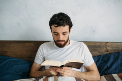 Bearded man reading a big book lying in his bedroom. Serious guy in white shirt is reeling off interesting and exciting adventure story. Close up Stock Photos