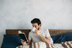 Bearded man reading a big book lying in his bedroom. Smiling guy is reeling off pages one by one and drinking hot tea or coffe in the same time Stock Photography