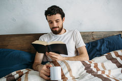 Bearded man reading a big book lying in his bedroom. Smiling man reading an interesting book lying in his bedroom under the blanket. Cute guy holding cup of tea Stock Photography
