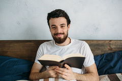 Bearded man reading a big book lying in his bedroom. Bearded man reading a big book lying in his bedroom under the blanket and holding it with both hands Stock Photo