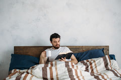 Bearded man reading a big book lying in his bedroom. Bearded man reading a big book lying in his bedroom under the blanket. Nice guy holding paperback in left Royalty Free Stock Photos