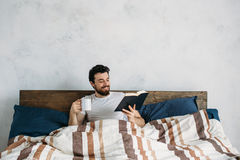 Bearded man reading a big book lying in his bedroom. Young guy holding paperback and being under the blanket. He is enjoying with story Royalty Free Stock Photos