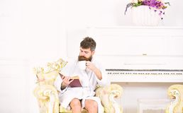 Man reading book while drinking coffee or tea. Rich guy sitting in antique armchair. Enjoying perfect day. Bearded man reading book while drinking coffee or tea royalty free stock photography