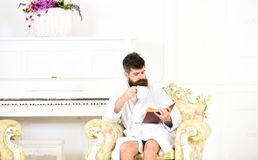 Man reading book while drinking coffee or tea. Rich guy sitting in antique armchair. Enjoying perfect day. Bearded man reading book while drinking coffee or tea Royalty Free Stock Photos