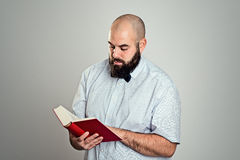 Bearded man reading a book in front of gray background Royalty Free Stock Images