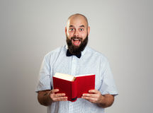 Bearded man reading a book in front of gray background Stock Photography