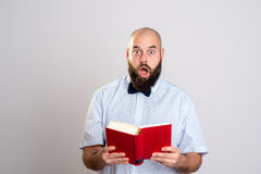 Bearded man reading a book in front of gray background Stock Image