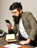 Bearded man in reading glasses with smartphone. Scientist hipster with mobile phone and book. Businessman in suit read. At desk. Teacher with long beard on stock photos