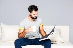 Bearded man reading magazine Stock Photo