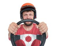 Bearded man in red helmet with steering wheel, isolated on white background. Stock Image