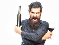 Bearded man with red wine. Handsome bearded rich man with stylish hair mustache and long beard on angry face in blue fashion shirt holding glass of red wine and stock photos