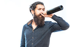Bearded man with red wine. Handsome bearded rich man with stylish hair mustache and long beard on serious face in blue fashion shirt drinking from bottle royalty free stock photography