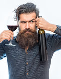 Bearded man with red wine. Handsome bearded rich man with stylish hair mustache and long beard on serious face in blue fashion shirt holding glass of red wine royalty free stock photography