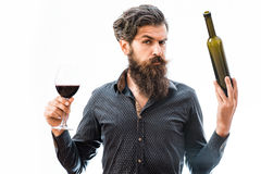Bearded man with red wine. Handsome bearded rich man with stylish hair mustache and long beard on serious face in blue fashion shirt holding glass of red wine stock photo