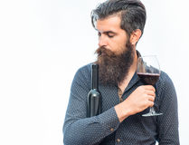 Bearded man with red wine. Handsome bearded rich man with stylish hair mustache and long beard on serious face in blue fashion shirt holding glass of red wine stock photography