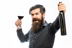 Bearded man with red wine. Handsome bearded rich man with stylish hair mustache and long beard on smiling face in blue fashion shirt holding glass of red wine royalty free stock photo