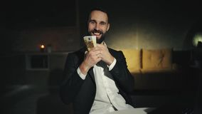 A bearded businessman is working at home with laptop and holding a big wad of cash. An adult man is smiling. He`s happy. stock footage