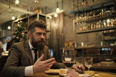 Bearded man in restaurant with companion. Business on go and communication. Confident bar customer speak in cafe. Date. Or business meeting of hipster in pub stock photography