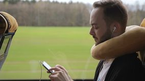 Bearded man rides bus, holding smartphone and listening to music on headphones. Young guy looks closely at phone screen, touching it with fingers. Brunet stock video footage