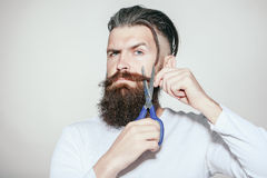 Bearded man with scissors Royalty Free Stock Photography