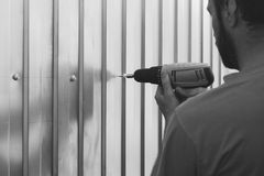 A bearded man with a screwdriver in his hands is screwed with self-tapping sheets of metal profile. Selective focus black and white photo Stock Photography
