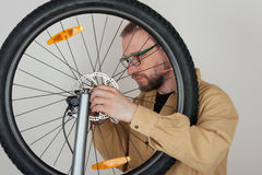 Bearded man screws the front wheel on the mtb bicycle. Royalty Free Stock Photo