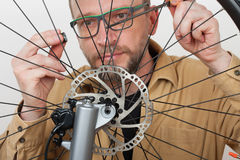 Bearded man screws the front wheel on the mtb bicycle. Royalty Free Stock Image