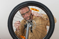 Bearded man screws the front wheel on the mtb bicycle. Stock Photo