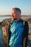 Bearded man on sea coast. Traveler on the sea coast rests  and looks at the sun Stock Photography
