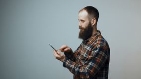 Man sending a sms on cell phone. Bearded man sending a sms on cell phone, turning and smiling at camera stock footage