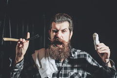 Bearded man shaves with razor. Amazed man, handsome, bearded hipster, brunette with long beard and moustache shaves with vintage razor with open blade and stock photo