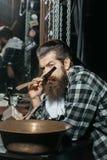 Bearded man shaves with razor Royalty Free Stock Image