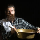 Bearded man shaves with razor. Handsome man, bearded hipster, brunette with long beard and moustache shaves with open vintage razor with blade and copper basin royalty free stock photography